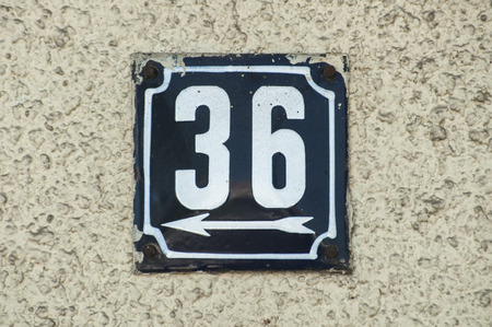 Weathered grunge square metal enameled plate of number of street address with number 36 closeup
