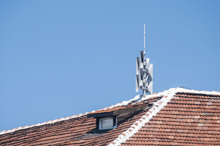 Roof of vintage house covered with ceramic tiles and horns for outdoor warning systems on clear blue sky background