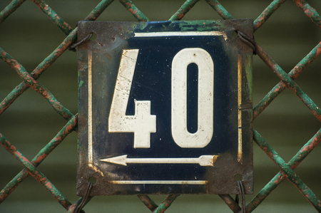 Weathered grunge square metal enameled plate of number of street address with number 40 closeup
