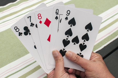Female hand holding five different playing cards closeup
