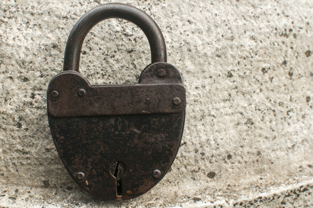 Old weathered grunge retro locked padlock closeup on solid stone surface background Banco de Imagens