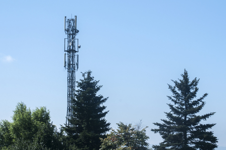 Cell phone antenna on aerial tower used for GSM and UMTS mobile phone transmissions among trees on blue sky background Stock Photo