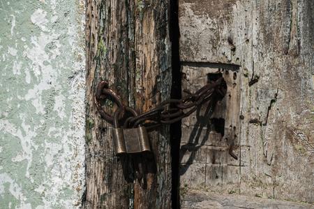 Old locked retro padlock and iron chain of grunge wooden rural door closeup