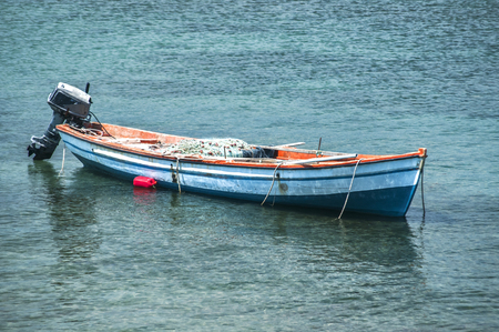 Fishing boat anchored in calm blue sea waters closeup in sunny summer day