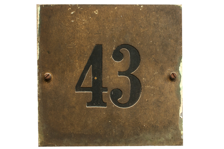 Old retro weathered cast iron plate with street number 43 closeup isolated on white background