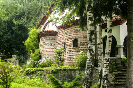 Orthodox medieval byzantine style church facade and green monastery garden