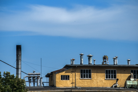 Top of obsolete vintage industrial building and facilities on blue sky background