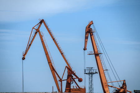 Industrial scene with river port crane facilities on blue sky background