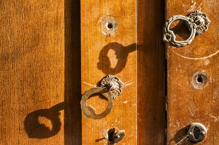 Old aged wooden neglected wardrobe door retro metal handles closeup