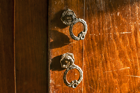 Old aged wooden neglected wardrobe door retro metal handles closeup 写真素材