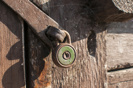 Old vintage weathered gunge locked padlock closeup on wooden background