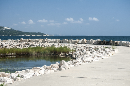 Seaside promenade with white stones on clear sunny summer day Stock Photo