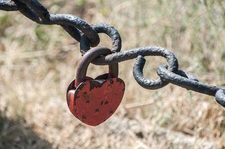 Old retro vintage iron chain links and locked padlock closeup