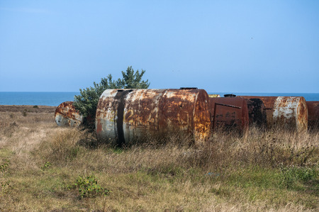 Old abandoned weathered aged corroded fuel tanks on seashore landscape in clear sunny summer day Stock Photo - 127453844