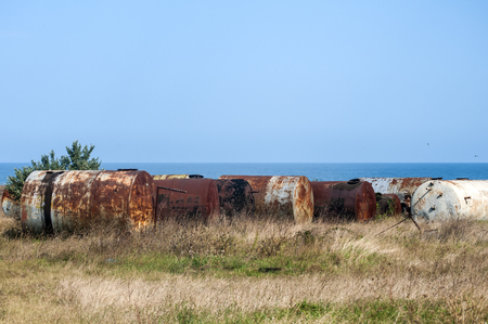 Old abandoned weathered aged corroded fuel tanks on seashore landscape in clear sunny summer day