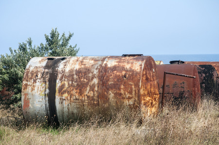 Old abandoned weathered aged corroded fuel tanks on seashore landscape in clear sunny summer day Stock Photo - 127453848