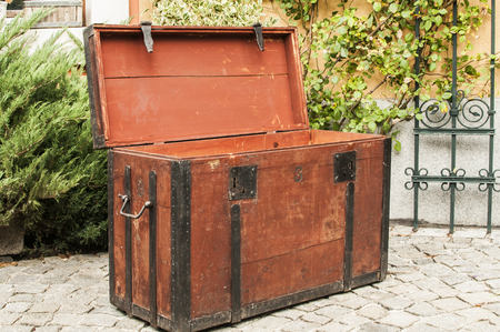 Old vintage retro wooden chest with iron strapping on stone paved house backyard