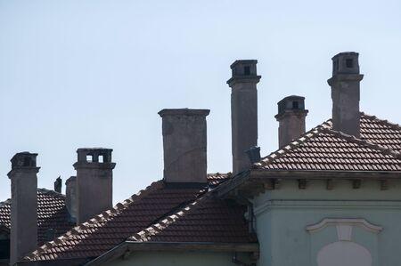 Dachy domów i kominy na jasnym tle błękitnego nieba