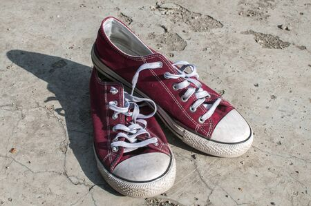 Pair of worn out vintage red old canvas sneakers on outside concrete surface Stock Photo