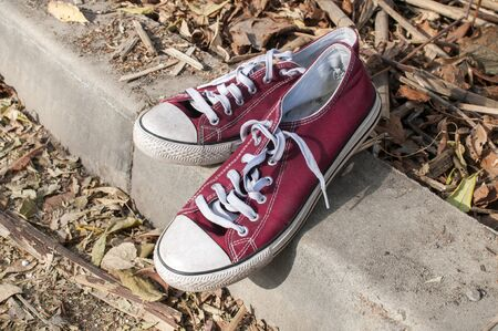 Pair of worn out vintage red old canvas sneakers on dry autumn leaves surface