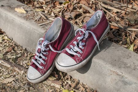 Pair of worn out vintage red old canvas sneakers on dry autumn leaves surface Stock Photo - 125904292