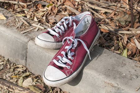 Pair of worn out vintage red old canvas sneakers on dry autumn leaves surface Stock Photo - 125904294
