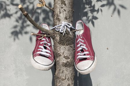Pair of worn out vintage red old canvas sneakers hanging on their laced ties