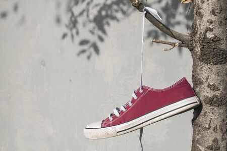 Red worn out vintage old canvas sneaker hanging on his laced ties