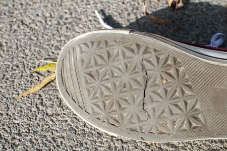 A sneaker cracked rubber outsole closeup on asphalt background
