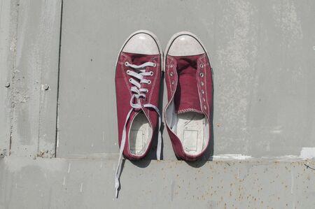 Paire de vieilles baskets en toile rouge vintage usé sur fond de surface en étain peint en gris