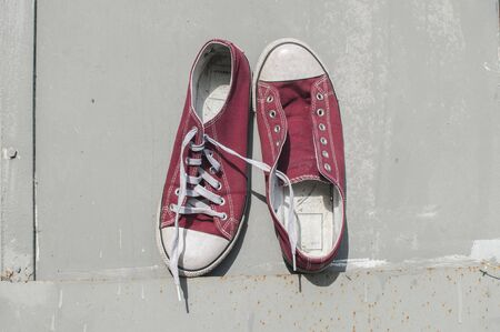 Pair of worn out vintage red old canvas sneakers on grey painted tin surface background Stock Photo