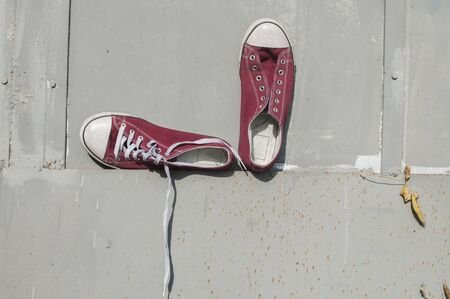 Pair of worn out vintage red old canvas sneakers on grey painted tin surface background Stock Photo - 126450575