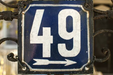 Weathered grunge square metal enameled plate of number of street address with number 49 closeup isolated on white background