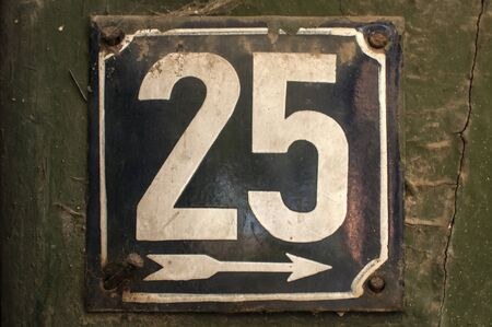 Weathered grunge square metal enameled plate of number of street address with number 25 closeup