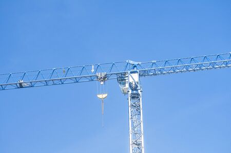 High rise building tower crane closeup on blue sky background Stock Photo