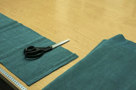 Scissors, centimeter ruler and prepared for cutting fabric on table in sewing workshop