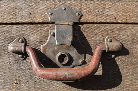 Old weathered retro vintage grunge suitcase handle and metal latch lock closeup