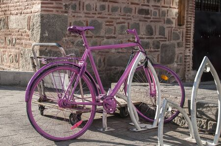 Pink painted bicycle locked on bike stand