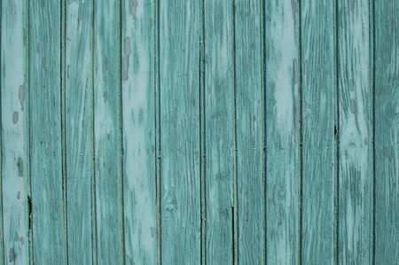 Old weathered grunge green painted wooden boards wall closeup as background