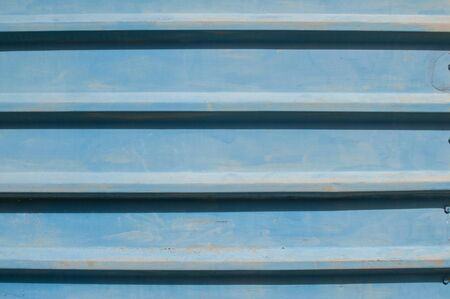 Weathered blue painted tin corrugated steel sheet closeup as metal background