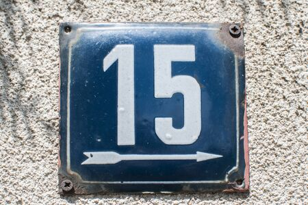 Weathered grunge square metal enameled plate of number of street address with number 15 closeup