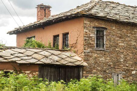 Old rural country house with roof stone slabs closeup