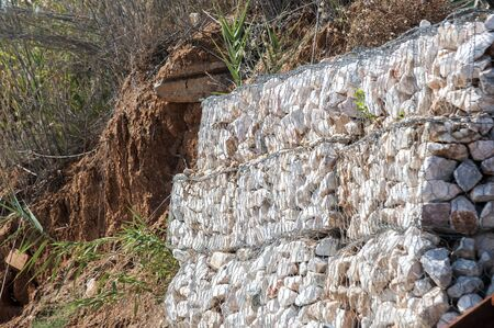 Gabion galvanized wire mesh box with stones on eroded seaside Stock Photo