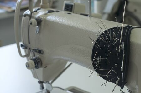 Needle and foot of sewing machine closeup as manufactoring background