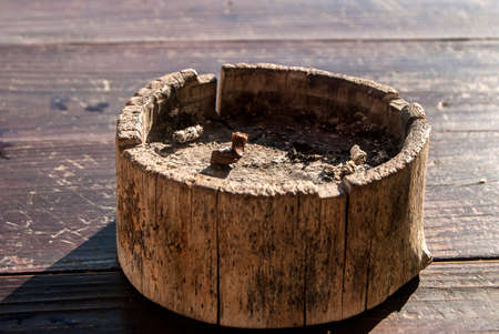 Wooden ash tray with cigarette butt closeup Stock Photo