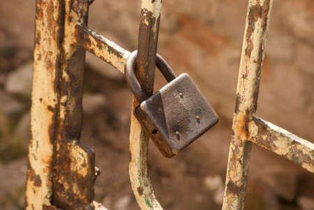 Rusty weathered padlock locked on aged grunge metal garden door closeup Standard-Bild