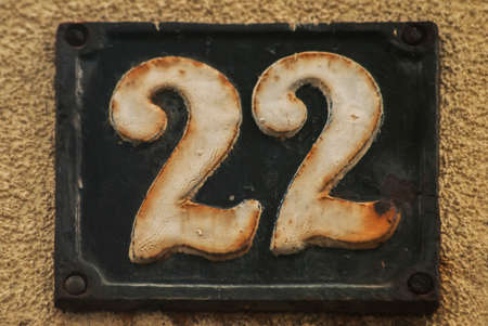 Old retro weathered cast iron plate with number 22 closeup