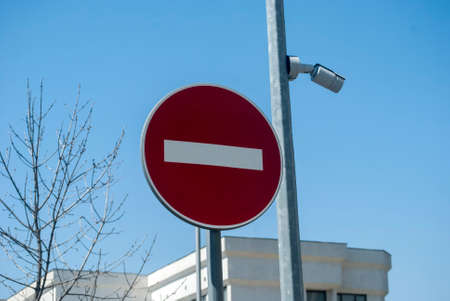 Red traffic road stop sign and pole with security camera closeup on blue sky background
