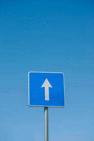 Blue rectangle one way road traffic sign closeup on blue sky background Standard-Bild