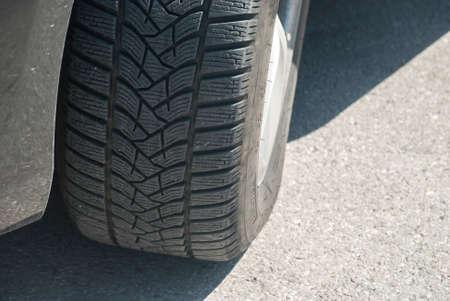 Car tyre on asphalt road surface closeup